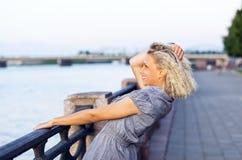 Glückliche blonde Frau im grauen Kleid. Stockbilder