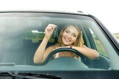 Glückliche blonde Frau im neuen Auto, das Tasten zeigt Stockfoto