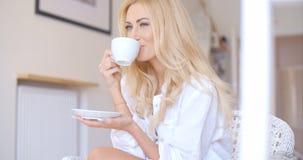 Glückliche blonde Frau im weißen trinkenden Kaffee Stockbild