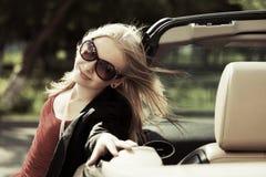 Glückliche blonde Frau am konvertierbaren Auto Lizenzfreie Stockfotos