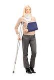 Glückliche blonde Frau mit defekter Armholding eine Krückenaufstellung Stockfoto