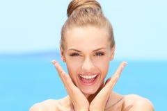 Glückliche blonde Frau mit den Händen auf Chin Lizenzfreie Stockbilder