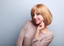 Glückliche blonde Frau mit der kurzen Frisur, die mit der Hand nahe f schaut Stockfotos