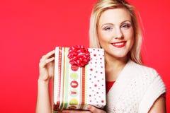Glückliche blonde Frau mit einem Geschenk Lizenzfreies Stockfoto