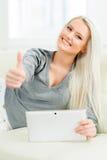 Glückliche blonde Frau mit einem Tablet-Computer Lizenzfreie Stockfotos