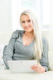 Glückliche blonde Frau mit einer Tablette Stockbild