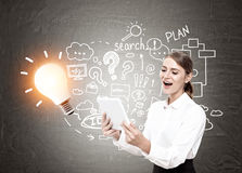 Glückliche blonde Frau mit einer Tablette, Ideen und Plänen Lizenzfreie Stockfotos