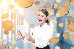 Glückliche blonde Frau mit einer Tablette, Münzenregen Stockfoto