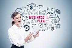 Glückliche blonde Frau mit einer Tablette, Unternehmensplan Stockfotografie