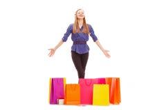 Glückliche blonde Frau mit Einkaufstaschen auf dem Boden Lizenzfreies Stockbild