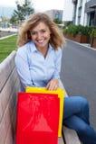 Glückliche blonde Frau mit Einkaufstaschen in der Stadt Stockfotos