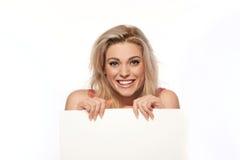 Glückliche blonde Frau mit leerem Zeichen Stockfotografie