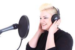 Glückliche blonde Frau mit Mikrofon Stockfotos