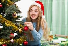 Glückliche blonde Frau in Sankt-Hut nahe Weihnachtsbaum Stockfotos