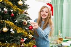 Glückliche blonde Frau in Sankt-Hut nahe Weihnachtsbaum Lizenzfreie Stockfotografie
