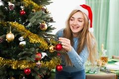 Glückliche blonde Frau in Sankt-Hut nahe Weihnachtsbaum Stockfotografie