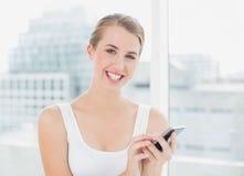 Glückliche blonde Frauenversenden von sms-nachrichten Lizenzfreie Stockbilder