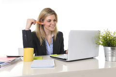 Glückliche blonde Geschäftsfrau, die an Computer am Schreibtischlächeln arbeitet Lizenzfreie Stockbilder