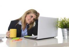 Glückliche blonde Geschäftsfrau, die an Computer am Schreibtischlächeln arbeitet Stockfotos