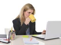 Glückliche blonde Geschäftsfrau, die an Computerlaptop mit Kaffeetasse arbeitet Stockfotografie