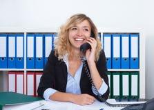 Glückliche blonde Geschäftsfrau im Büro am Telefon Lizenzfreie Stockbilder