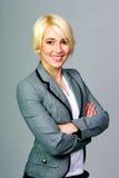 Glückliche blonde Geschäftsfrau mit den Armen faltete Stellung Lizenzfreie Stockbilder