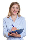 Glückliche blonde Geschäftsfrau mit Klemmbrett Stockfotografie