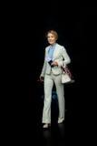 Glückliche blonde Geschäftsfrau mit Pass und Flugticket in der weißen Klage bereit auszulösen Lizenzfreie Stockfotografie