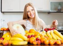 Glückliche blonde Hausfrau mit reifen Früchten Stockbild