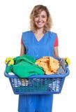 Glückliche blonde Hausfrau mit schmutziger Kleidung Stockbild