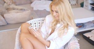 Glückliche blonde jugendlich Frau auf dem Stuhl beschäftigt mit Telefon Lizenzfreie Stockfotos