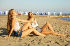 Glückliche blonde Jugendliche, die vor dem Meer bei Sonnenuntergang sich entspannen Stockbilder