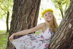 Glückliche blonde junge Frau beim Parklächeln Lizenzfreie Stockfotografie