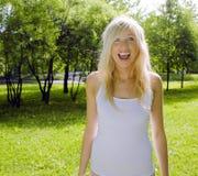 Glückliche blonde junge Frau beim Parklächeln Stockfotografie
