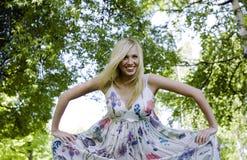 Glückliche blonde junge Frau beim Parklächeln Lizenzfreies Stockbild