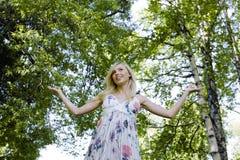 Glückliche blonde junge Frau beim Parklächeln Stockfotos