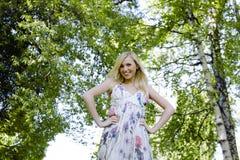 Glückliche blonde junge Frau beim Parklächeln Stockfoto