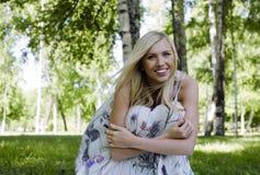Glückliche blonde junge Frau beim Parklächeln Stockbild