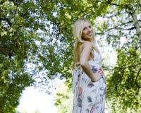 Glückliche blonde junge Frau beim Parklächeln Lizenzfreie Stockbilder