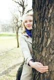 Glückliche blonde junge Frau beim Parklächeln, Baum umarmend, Lebensstilleutekonzept Stockfotografie
