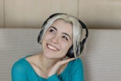 Glückliche blonde junge Frau, die auf Sofa mit Kopfhörer listeni sitzt Lizenzfreies Stockbild