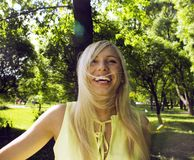 Glückliche blonde junge Frau im grünen Frühlingspark lächelnd, Lebensstil Stockfotografie