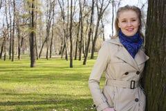 Glückliche blonde junge Frau im grünen Frühlingspark lächelnd, Lebensstil Lizenzfreie Stockfotos