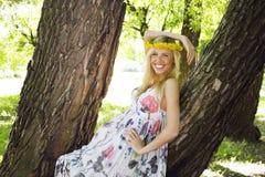 Glückliche blonde junge Frau im Park oben lächelnd, Blumenabschluß Stockfoto