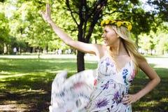 Glückliche blonde junge Frau im Park oben lächelnd, Blumenabschluß Stockfotos