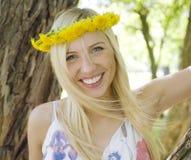 Glückliche blonde junge Frau im Park oben lächelnd, Blumenabschluß Lizenzfreies Stockbild