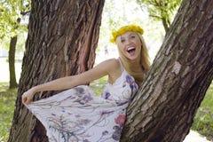 Glückliche blonde junge Frau im Park oben lächelnd, Blumenabschluß Stockfotografie