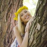 Glückliche blonde junge Frau im Park oben lächelnd, Blumenabschluß Lizenzfreie Stockfotografie