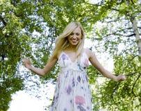 Glückliche blonde junge Frau im Park oben lächelnd, Blumenabschluß Stockbilder