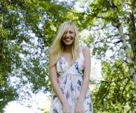 Glückliche blonde junge Frau im Park oben lächelnd, Blumenabschluß Lizenzfreie Stockbilder